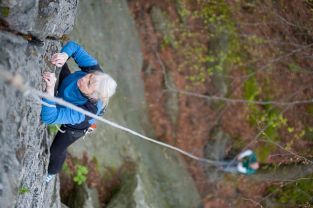 Woman practices in climbing at the rock in the mountains.