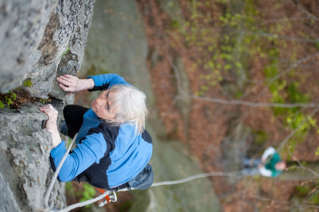 Woman practices in climbing at the rock in the mountains