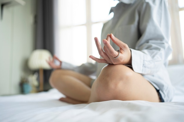 Woman practices meditation on the bed