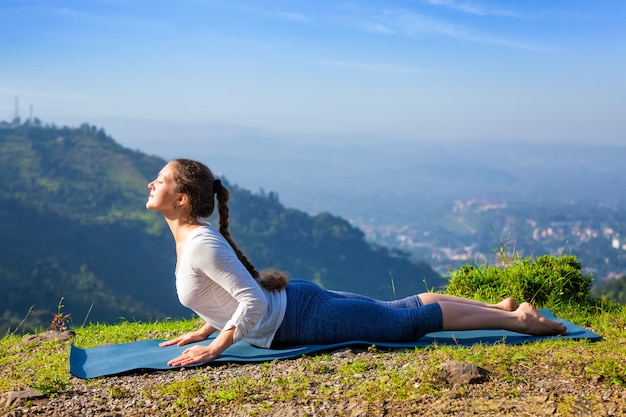 Woman practices yoga asana bhujangasana cobra pose