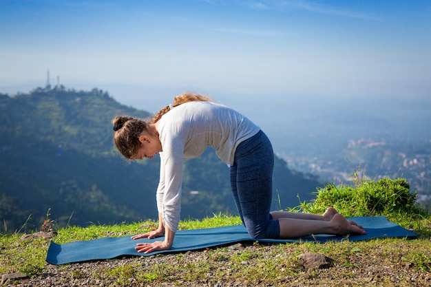 Woman practices yoga asana marjariasana outdoors
