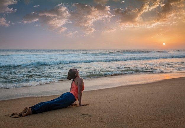 Woman practices yoga asana urdhva mukha svanasana at the beach