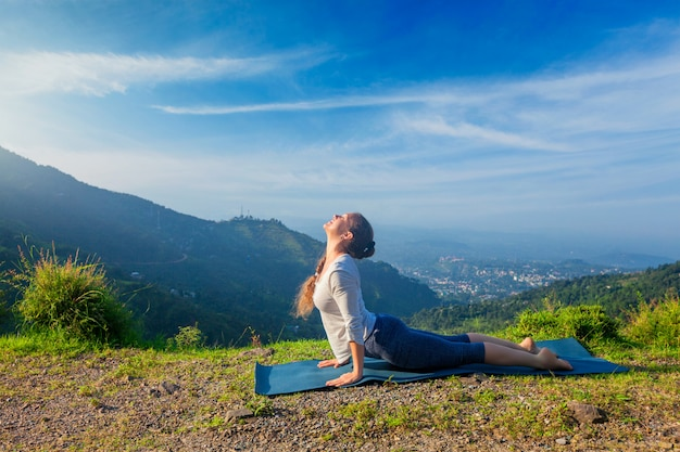 Woman practices yoga asana urdhva mukha svanasana outdoors