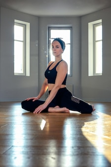 A woman practices yoga in a fitness room at dawn