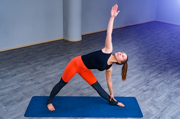 Женщина занимается йогой в тренажерном зале. спорт и здоровый образ жизни.