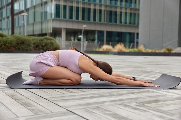 요가를 하는 여성은 운동복을 입은 팔을 앞으로 뻗고 피트니스 매트에서 무릎을 꿇고 도시 중심에서 야외에서 포즈를 취합니다.