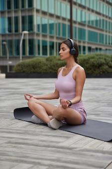 La donna pratica lo yoga medita in armonia fuori vicino all'edificio degli uffici si siede sul tappetino fitness ascolta musica tramite le cuffie gode di momenti di relax