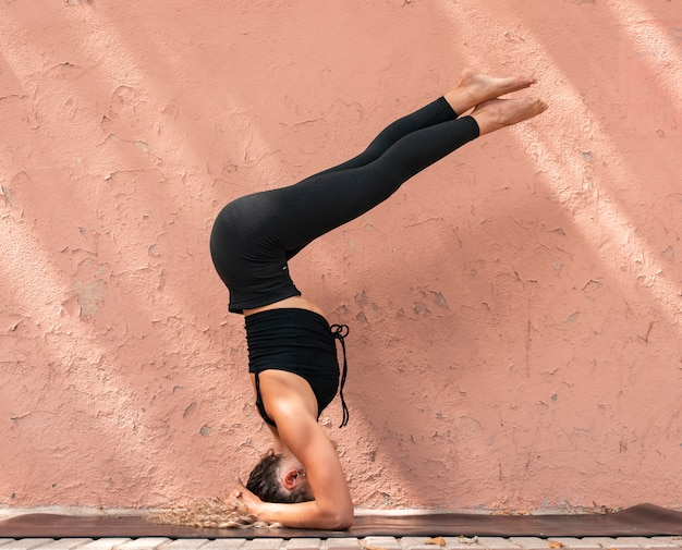 Woman practices yoga pose on a background wall