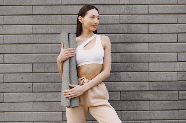 Woman practicing advanced yoga against a dark urban wall