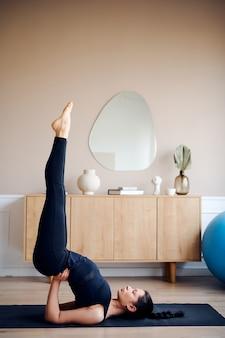 Женщина, практикующая продвинутую йогу дома