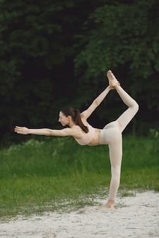 Woman practicing advanced yoga in a beach