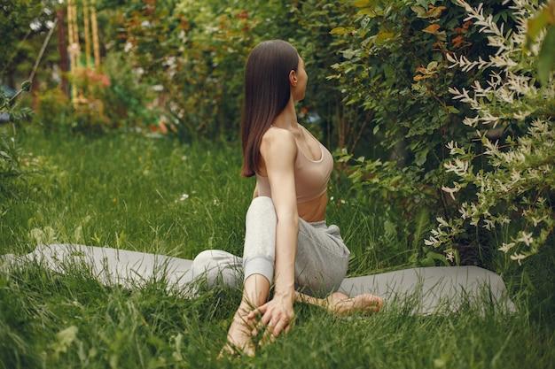 公園で高度なヨガの練習の女性