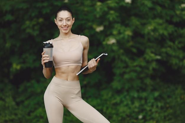 Женщина практикует передовые йоги в парке летом