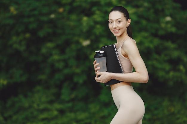 여름 공원에서 고급 요가 연습하는 여자