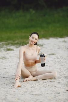 여름 해변에서 고급 요가 연습하는 여자