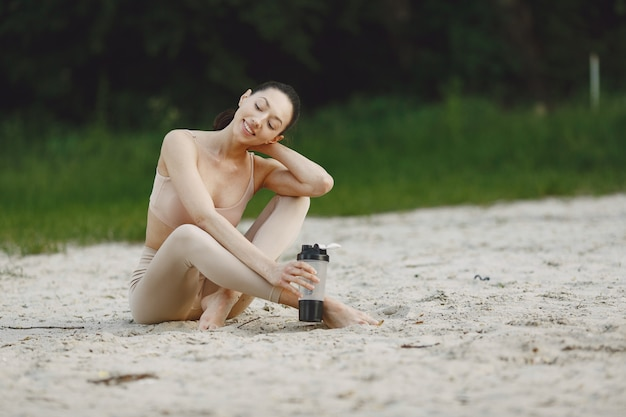 Woman practicing advanced yoga on a summer beach