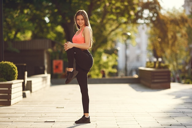Woman practicing advanced yoga in a summer city