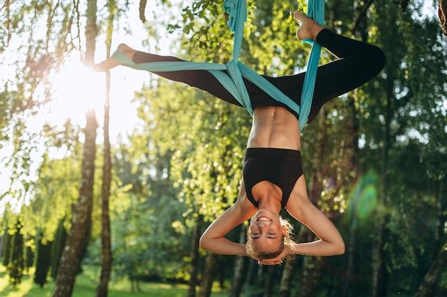Женщина, практикующая воздушную йогу на открытом воздухе. антигравитационный расслабляющий спорт. здоровье, концепция йоги летать.