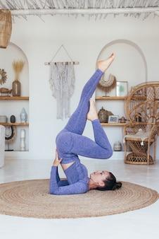 自宅で練習している女性は、足を上げて肩立ちをします。