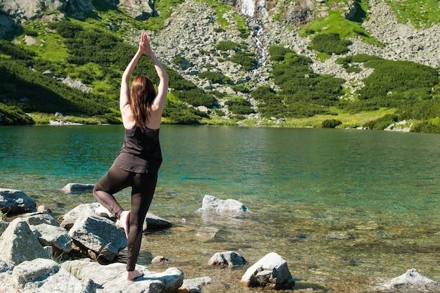 산속에 호수 근처 균형 요가 연습하는 여자
