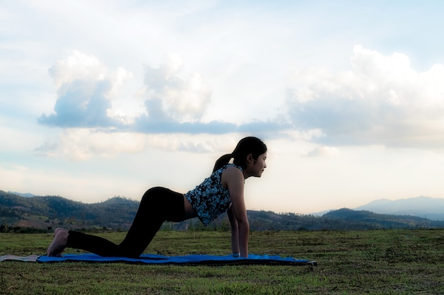 Woman practicing cow yoga pose outdoors over sunset sky background.