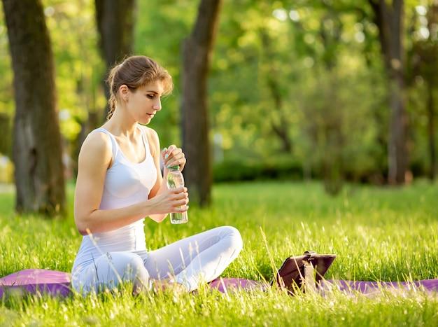 Женщина практикует фитнес и держит бутылку воды на коврик для йоги