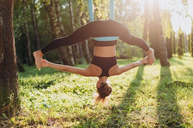 Женщина, практикующая йогу мухи на дереве, широко расставив ноги.