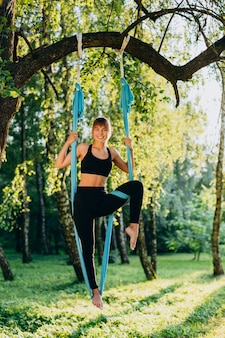 Woman practicing fly yoga  in park outdoors in standing pose looking at the camera
