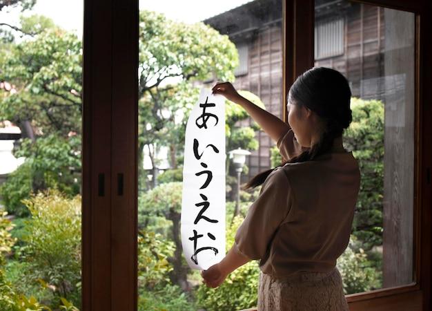 自宅で日本語の手書きを練習している女性