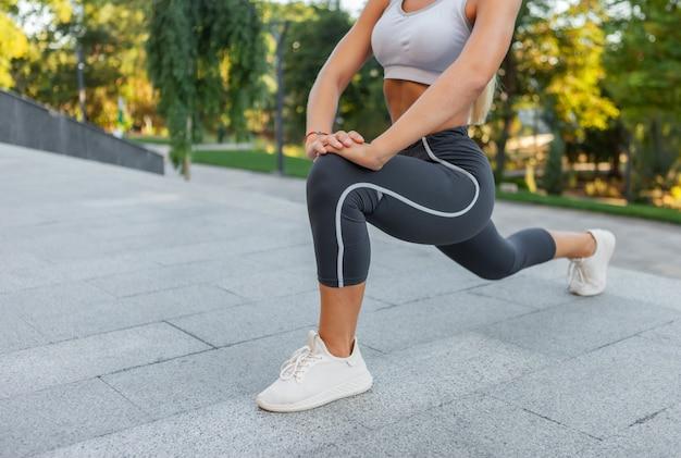 屋外トレーニングの前に脚のストレッチを練習している女性
