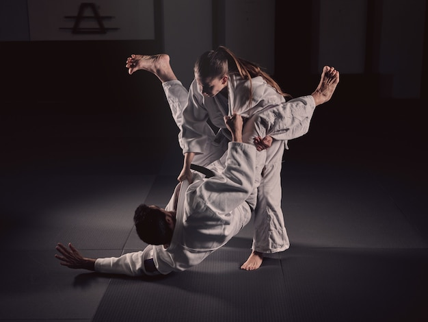 Woman practicing a martial arts chokehold with her trainer in kimonos