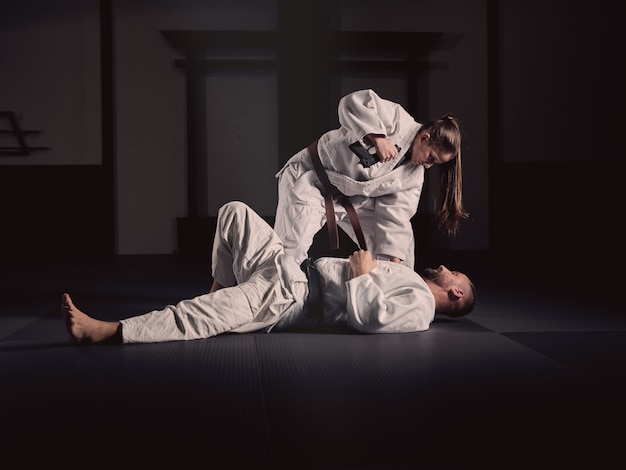 Woman practicing martial arts with her trainer in kimonos