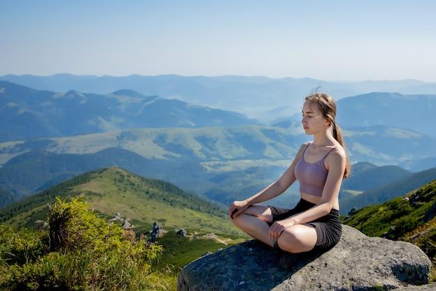 山で瞑想とヨガを練習している女性