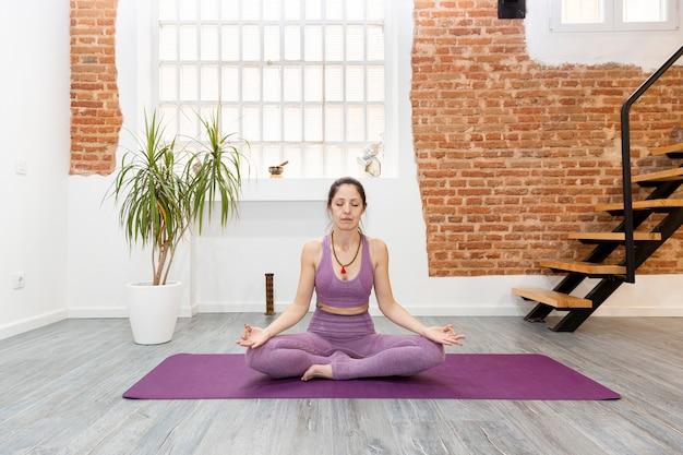 自宅でリラクゼーション運動を練習している女性。瞑想、ヨガ、ウェルネスの概念。テキスト用のスペース。 Premium写真