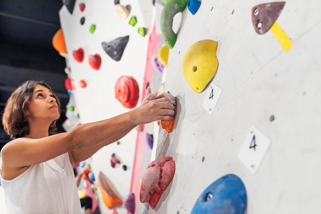 屋内で人工壁にロッククライミングを練習している女性。アクティブなライフスタイルとボルダリングのコンセプト。