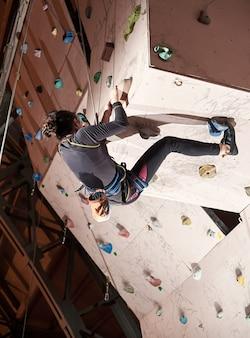 Женщина, практикующая скалолазание на каменной стене в помещении