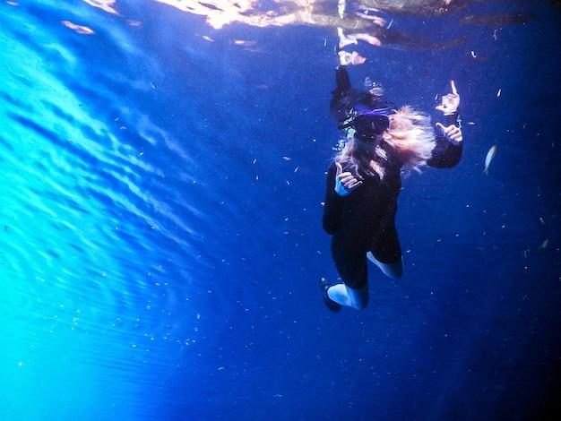 Женщина, практикующая скоркель в голубых водах