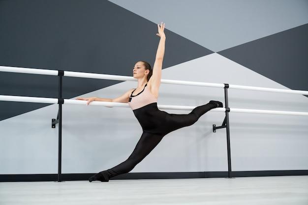 Woman practicing split holding handrails in dance studio