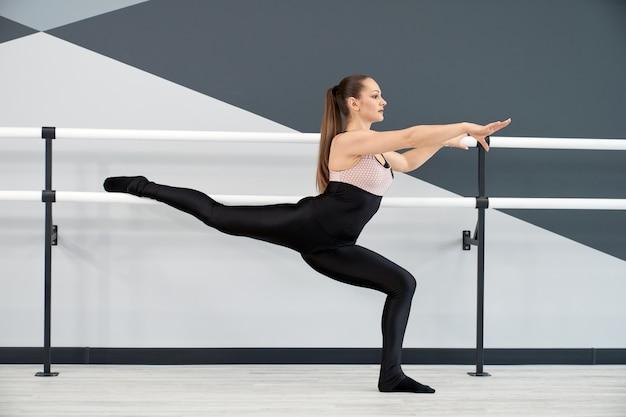 Женщина практикует сплит, держа поручни в танцевальной студии