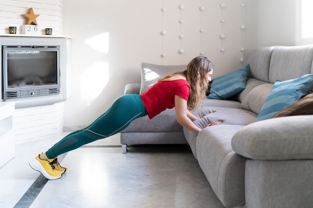Woman practicing sports doing push-ups on the sofa at home