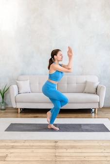 Женщина, практикующая стоя позу йоги дома на коврике