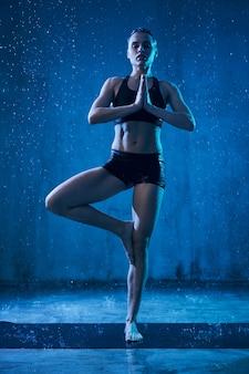 Woman practicing vrikshasana under rain