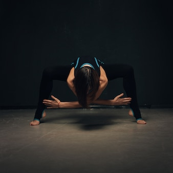 Woman practicing yoga against a dark texturized wall