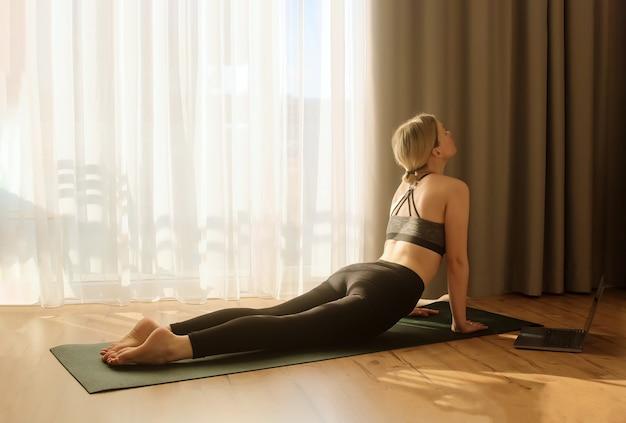 Женщина занимается йогой и растяжкой, занимаясь спортом, утренняя комната дома, поза собаки смотрит вверх Premium Фотографии