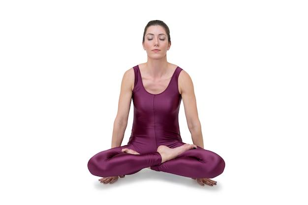 Woman practicing yoga in ardha padmasana pose