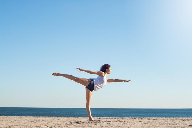 ビーチでヨガの練習の女性
