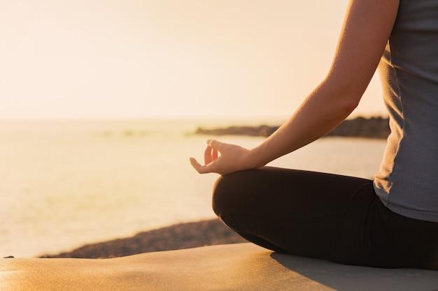 Женщина упражнениями йоги в свете заката.