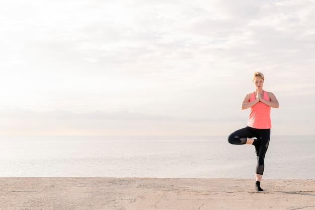 해돋이에 요가 균형을 연습하는 여자