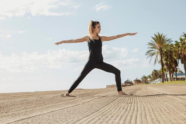 La donna a praticare yoga sulla spiaggia