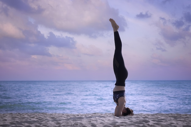 A woman practicing yoga on the beach